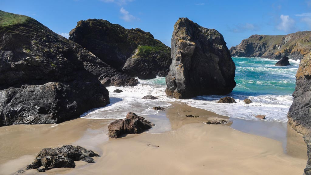 A beautiful blue tide washes up against the rocks at the cove.