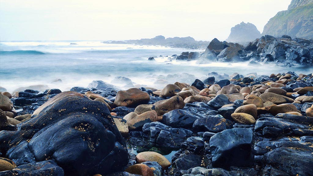 A long-exposure shot of Cape Cornwall's rocky beach.