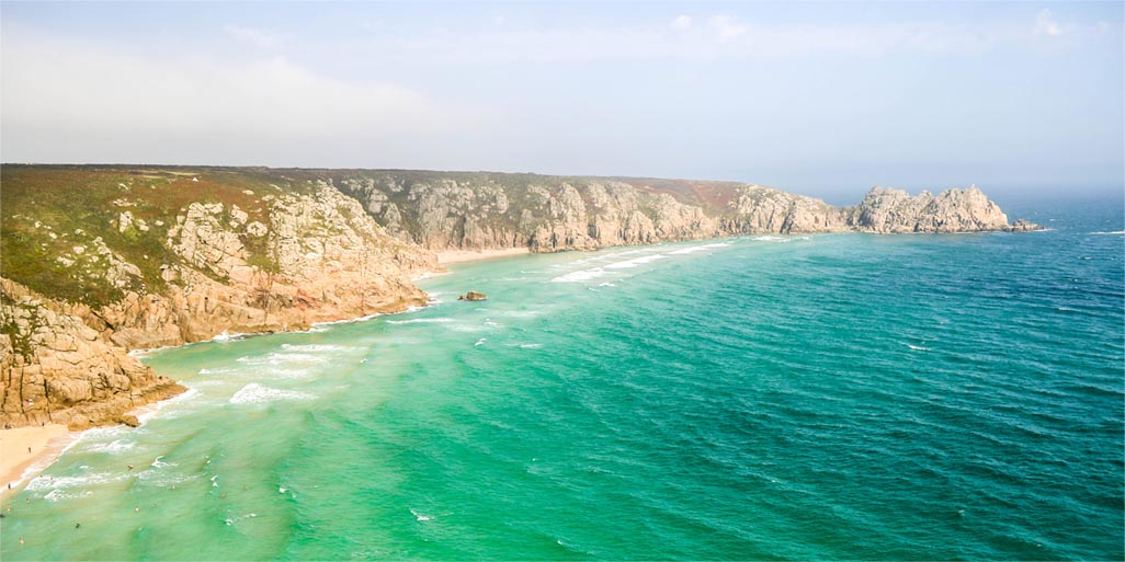 The wonderfully colourful tide with Logan Rock in the background at Porthcurno.