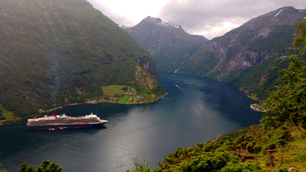 The enormous cruise ship was dwarfed by the formidable Geirangerfjord