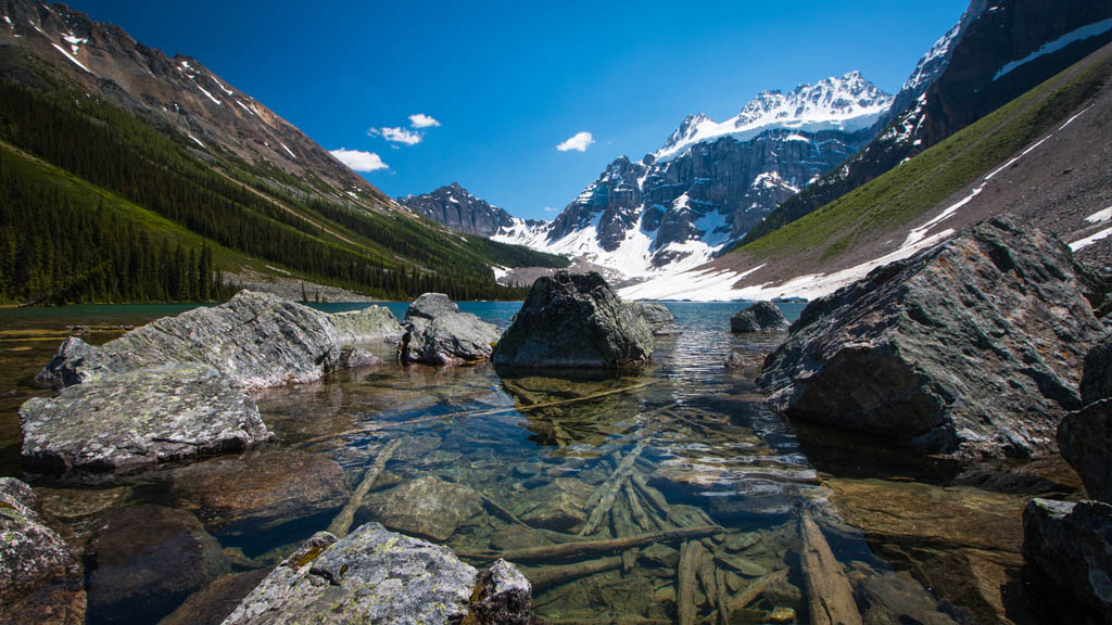 The almost disturbed feel of the Consolations Lakes, with rocks littered along the shore and the striking mountains in the background.