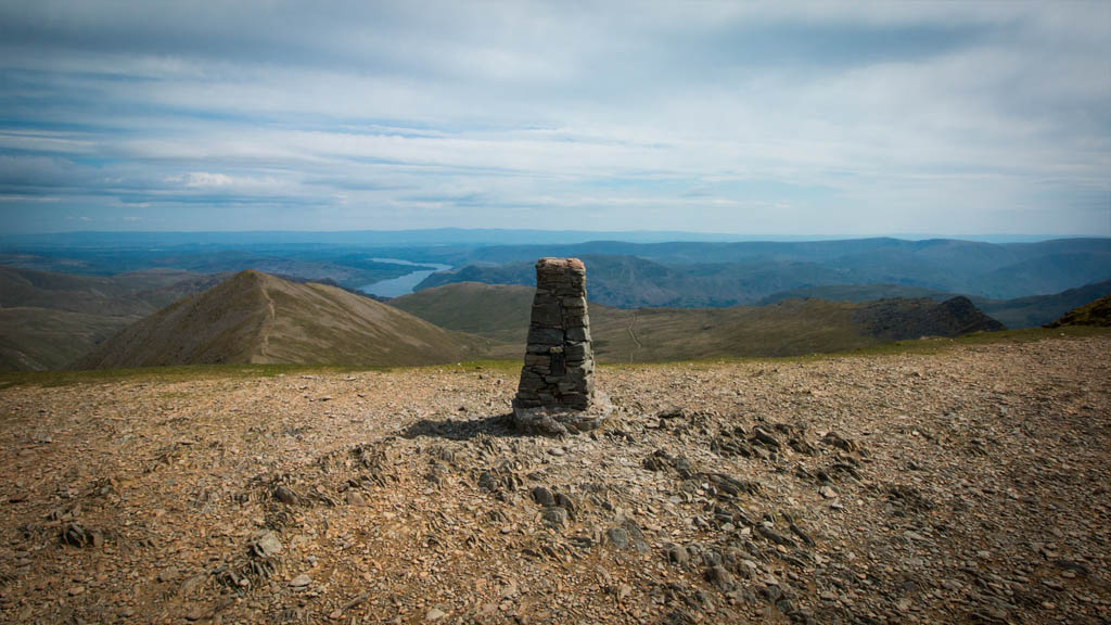 The trig point and summit of Helvellyn, with Ullswater clearly visible in the distance.